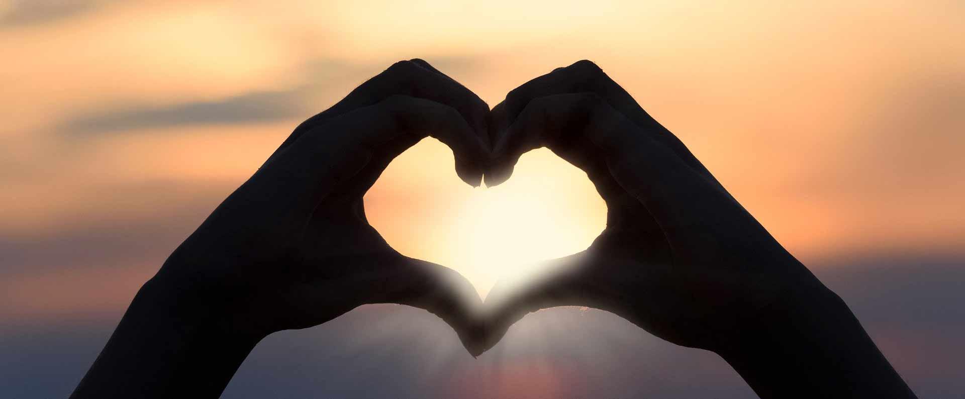 Hands making heart against sunset sky.