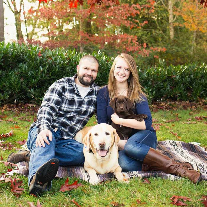 Brandon and his wife with his dogs smiling